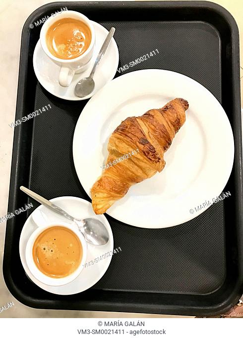 Two cups of coffee with croissant on a tray. View from above