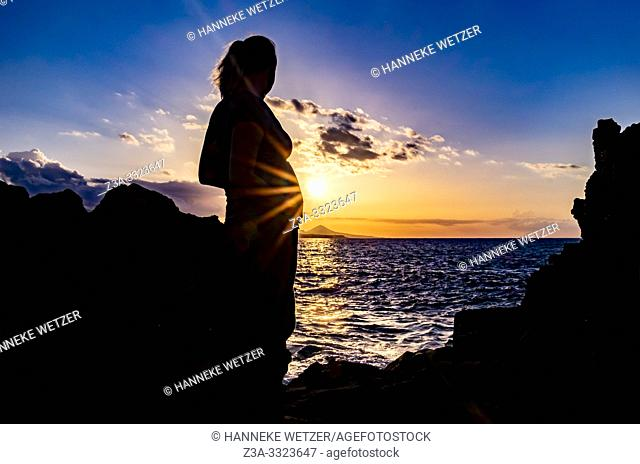 Silhouet of a pregnant woman during sunset at the coastline of Las Palmas de Gran Canaria, Canary Islands