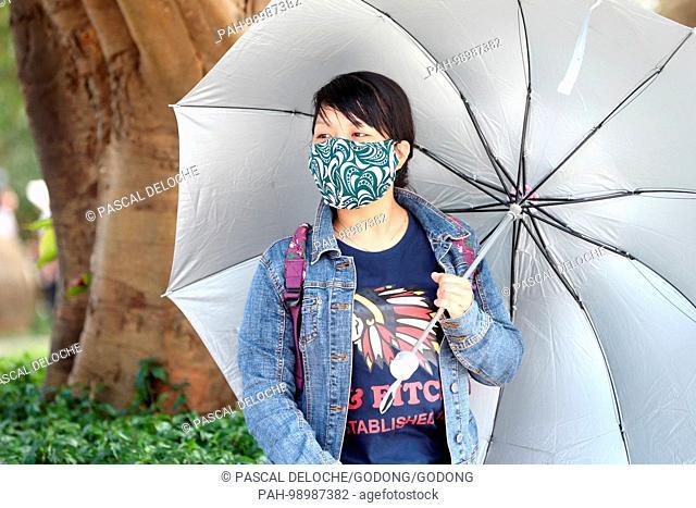 Young vietnamese woman with umbrella and mask. Danang. Vietnam. | usage worldwide. - Danang/South Central Coast/Vietnam