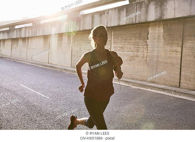 Silhouette female runner running on sunny urban street