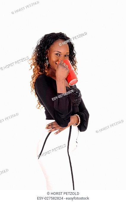 A gorgeous African American woman standing in a white skirt and black .blouse, drinking from a red mug, isolated for white background.