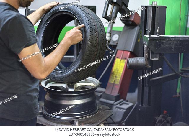 Professional mechanic using machine for tyre change