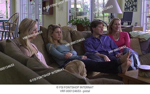 MS, DS, family of four sitting on a couch in their living room, watching TV