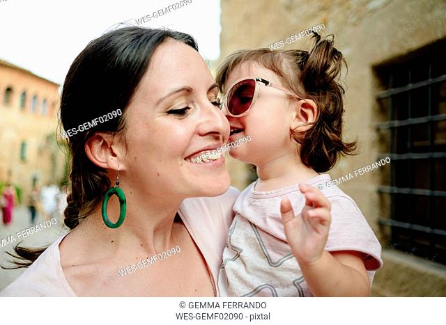 Happy baby girl wearing mother's sun glasses and kissing her