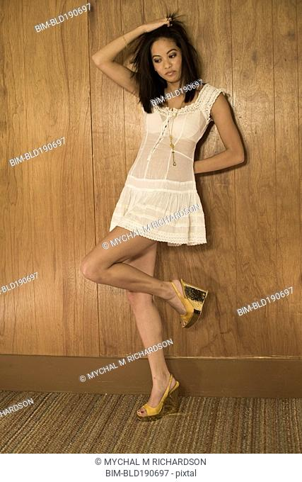 Asian woman leaning against wall