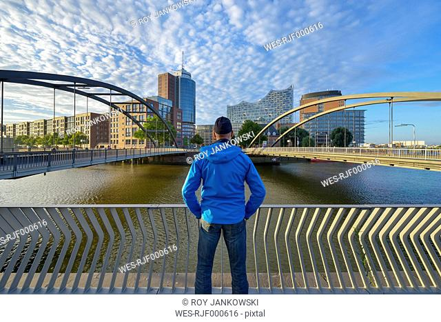 Germany, Hamburg, Man looking to Niederbaum bridge with Elbe Philharmonic Hall and Hanseatic Trade Center in the morning