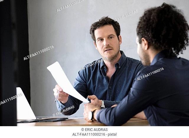 Men discussing document