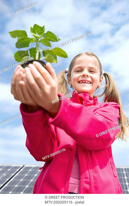 Portrait girl holding plant environmental protection