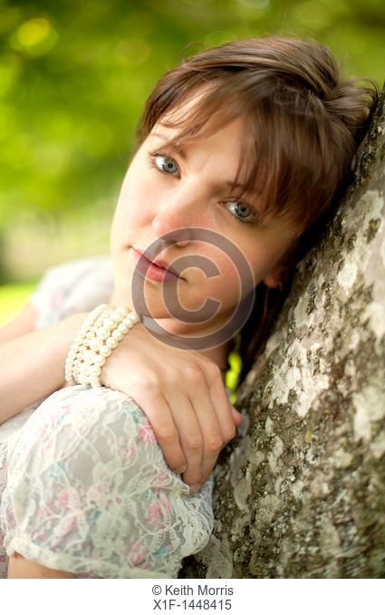 A young slim attractive girl in her late teens or early 20's, outdoors in a woodland glade  UK