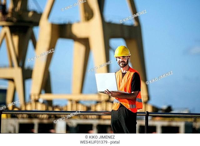 Portrait of smiling port worker using a laptop at work