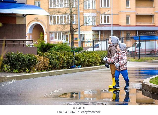 Two little boys, squat on a puddle, with little umbrellas. frienship communication concept