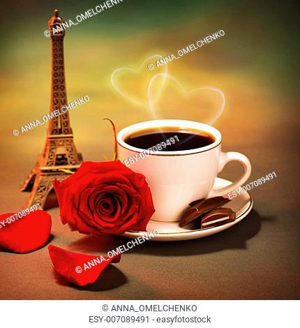 Conceptual photo of romantic trip to France, beautiful morning in Paris, food still life, cup of coffee with piece of chocolate and fresh red rose on the table...