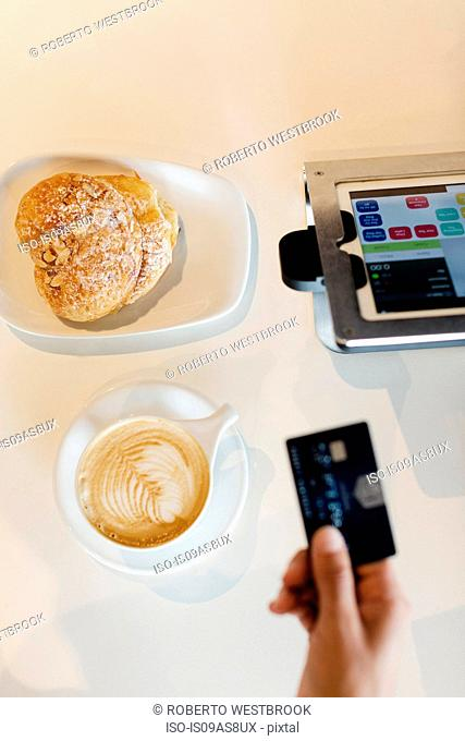 Customer paying for coffee in coffee shop, overhead view