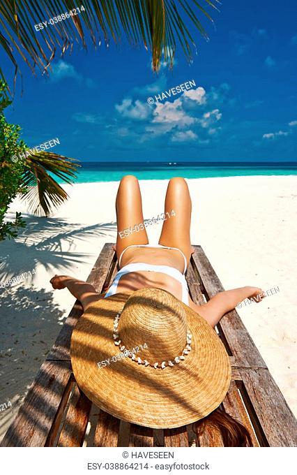 Woman at beautiful beach lying on chaise lounge