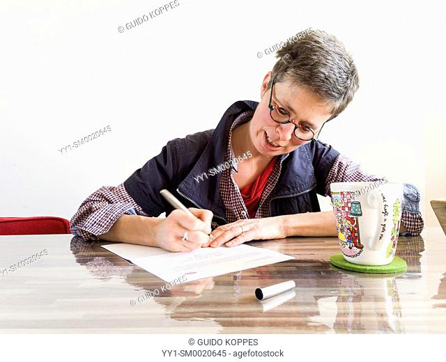 Tilburg, Netherlands. Mid adult caucasian woman, having multiple sclerosis or MS for over a decade, signing a release form during a photo report on her...
