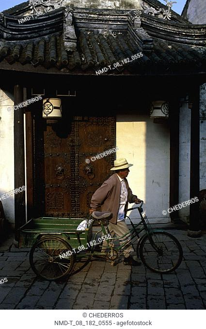 Side profile of a man pulling a cart in front of a house, China