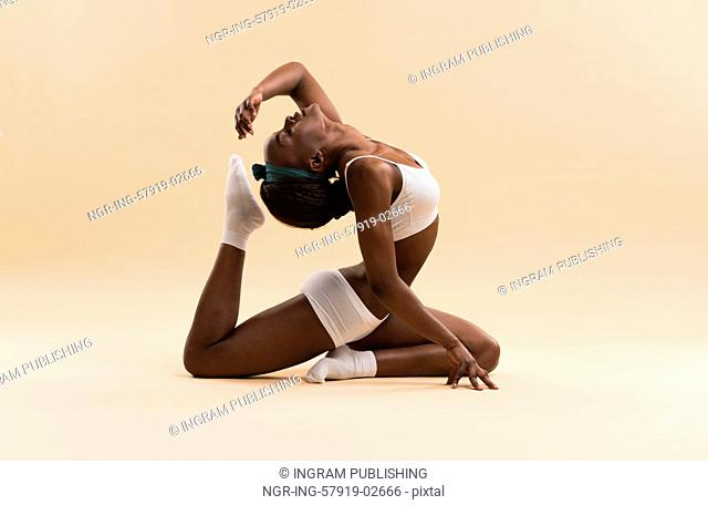 Young African woman doing yoga in stretching position