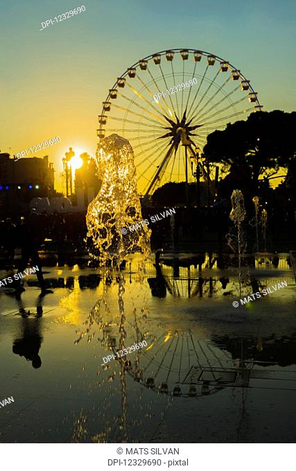 Fountain And A Ferris Wheel At Sunset Reflected In Water, Place Massena; Nice, Cote D'azur, France