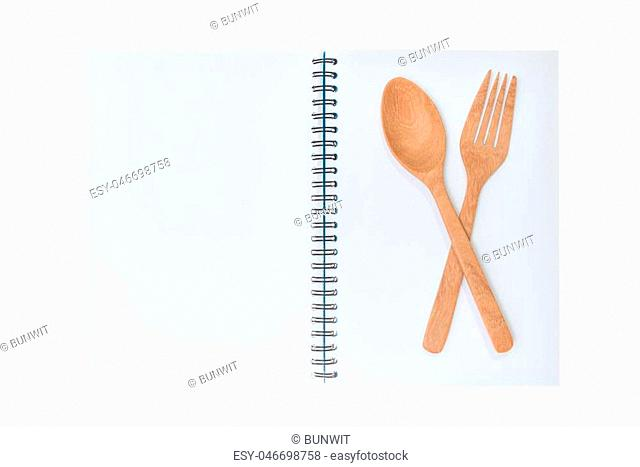 Blank notebook for recipe with wooden spoon and fork