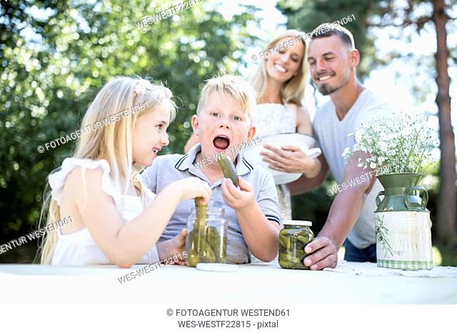 Portrait of boy with family eating gherkin outdoors