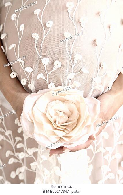 Close up of pregnant bride carrying bouquet
