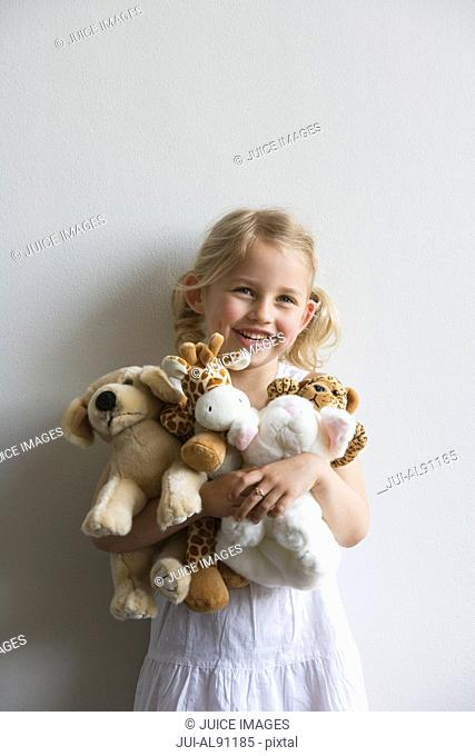 Preschool girl holding stuffed animals