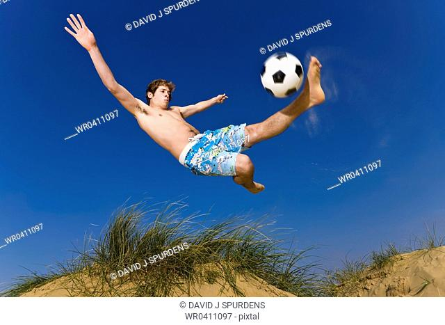 A beach soccer player takes a flying volley