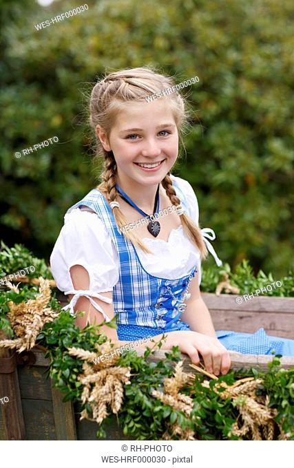 Germany, Luneburger Heide, portrait of smiling blond girl wearing dirndl sitting on harvest wagon