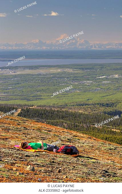 Female hiker resting on Blueberry Hill with Denali (Mt. McKinley) in the distance, Chugach State Park, Anchorage, Southcentral Alaska, Spring, HDR