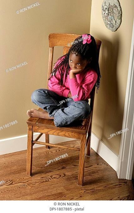 Girl on a chair in the corner