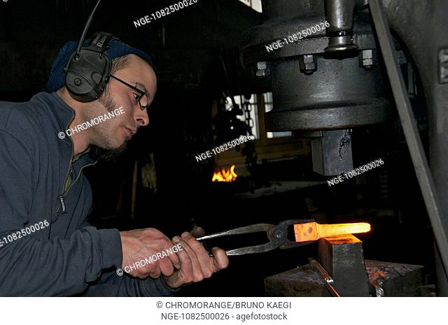 blacksmith working the steamhammer on redhot steel