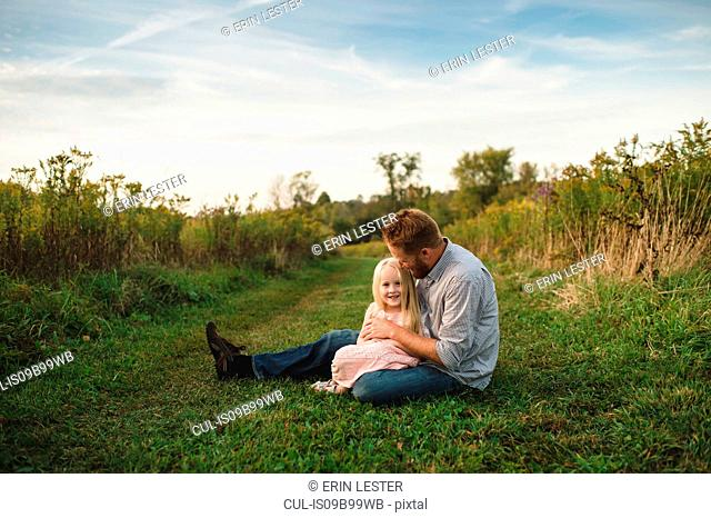 Daughter sitting on fathers lap on grass