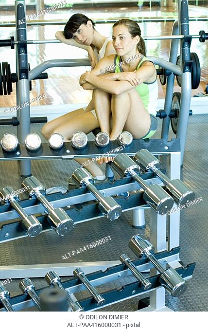 Two young women sitting in weight room