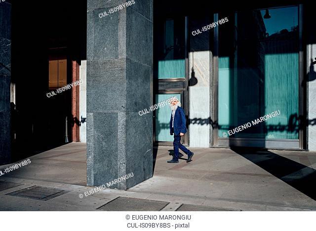 Senior businessman passing office building, Milano, Lombardia, Italy
