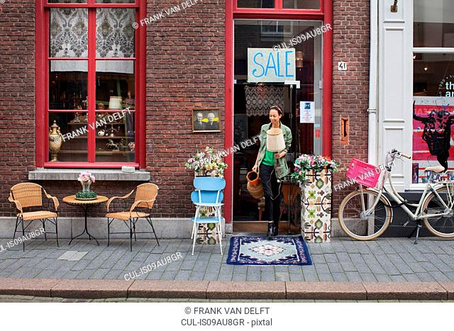 Young female customer with jug and lamp outside vintage shop