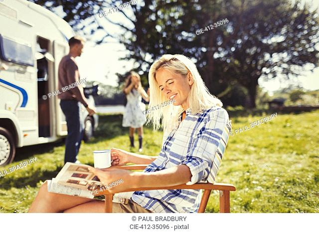 Woman reading magazine and drinking coffee outside sunny motor home