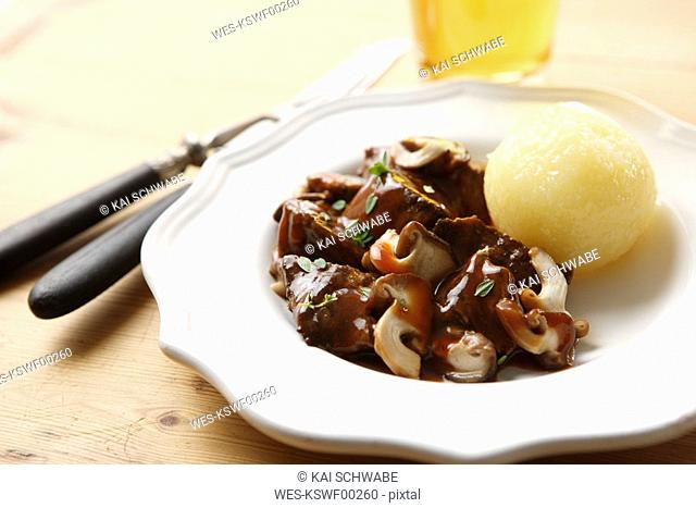 Venison goulash with mushrooms thyme and dumpling, close-up