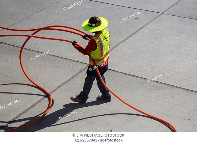 Tucson, Arizona - An electrical worker handles cables in the hot sun at Tucson International Airport