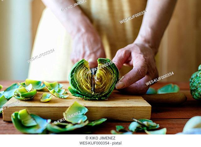 Woman's hands cutting an artichoke, close-up