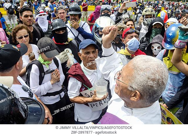 A priest blesses demonstrators on the freeway. Opposition protesters assembled on the Francisco Fajardo motorway, near Francisco de Miranda Air Force Base in La...