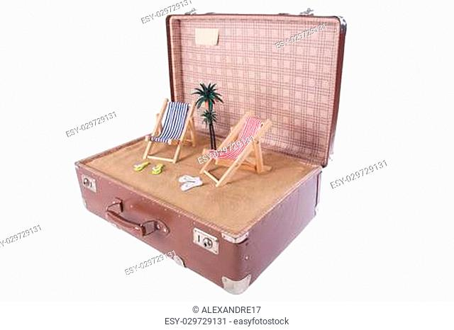 piece of the beach with a palm tree in an old suitcase over white