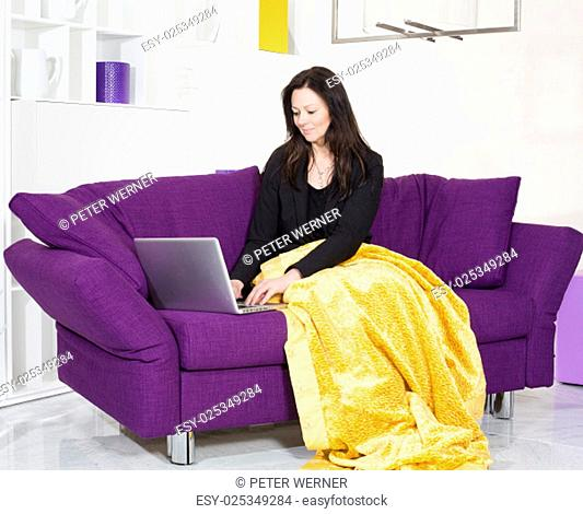 woman in black suit sitting on purple couch with a laptop
