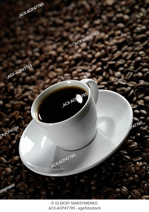 White cup of coffee with a saucer on roasted coffee bean background