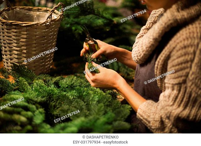 Florist woman decorating coniferous wreath