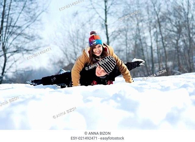 Young couple sledding on snow