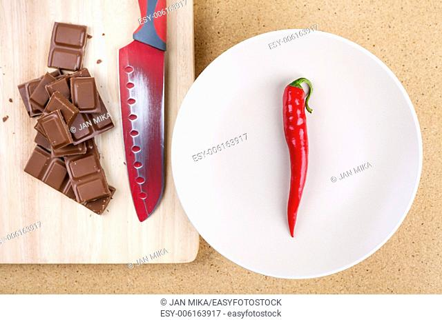 Fresh red hot chili pepper with chocolate and knife on chopping board