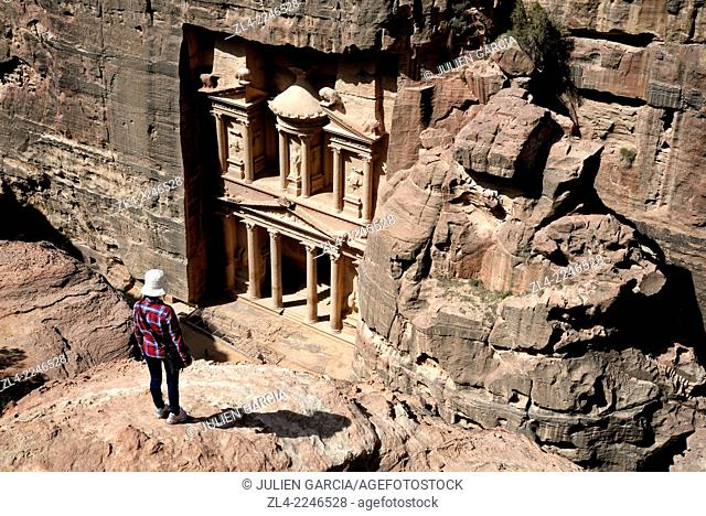 Woman watching the famous and elaborately carved façade of Al Khazneh (the Treasury), carved out of a sandstone rock face