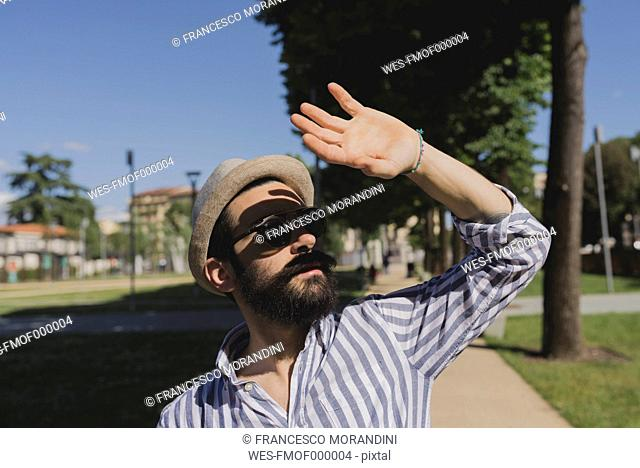 Young man with hat and sunglasses shielding his eyes