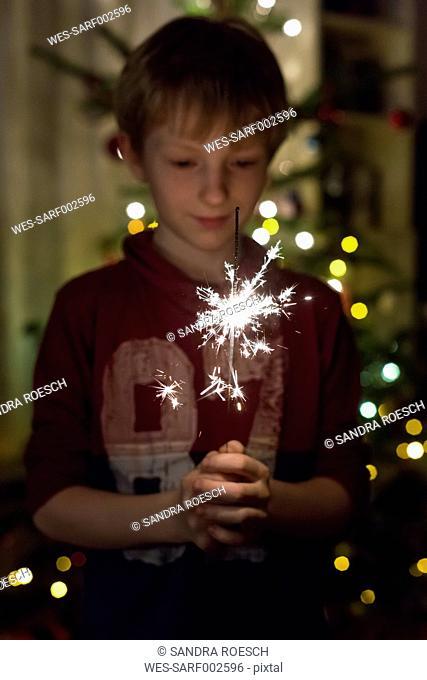 Boy holding sparkler at Christmas time