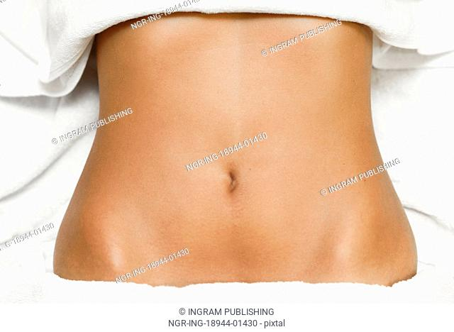 Top view of tan female abdomen laying on spa bed with white towels
